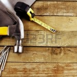 20585022-hammer-nails-tape-measure-and-saw-on-wood